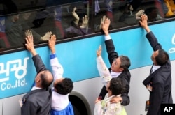 FILE - South Koreans on a bus touch the bus window in their attempt to feel the hands of their North Korean relatives as they bid farewell after the Separated Family Reunion Meeting at Diamond Mountain resort in North Korea, Oct. 26, 2015.