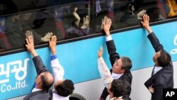 FILE - South Koreans on a bus touch the bus window in their attempt to feel the hands of their North Korean relatives as they bid farewell after the Separated Family Reunion Meeting at Diamond Mountain resort in North Korea.