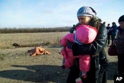 Seorang perempuan dan anaknya serta orang-orang lain lagi melewati mayat seorang pria yang tewas akibat ranjau darat dekat tempat penyeberangan ke daerah yang dikuasai pemerintah Ukraina, dekat Donetsk, Ukraina (10/2).