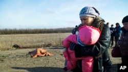 FILE - A woman with her child and others pass body of a man, who died in a land mine explosion near a frontline crossing to Ukrainian government-controlled territory, in the war conflict-hit Donetsk region, near Donetsk, eastern Ukraine, Feb. 10, 2015. The U.N. children's fund calls on Feb. 21, 2016, the daily suffering endured by more than one-half million Ukrainian children victimized by two years of conflict intolerable.