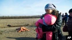 Žena sa detetom u Donjecku prolazi pored tela čoveka koji je stradao od nagazne mine