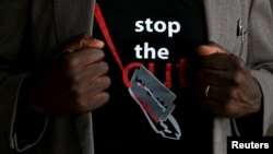 "FILE - A man's T-shirt reads ""Stop the Cut"" referring to Female Genital Mutilation during a social event advocating against such harmful practices at the Imbirikani Girls High School in Imbirikani, Kenya, April 21, 2016."
