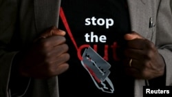 "FILE - A man's T-shirt reads ""Stop the Cut"" referring to Female Genital Mutilation during a social event advocating against the practice at the Imbirikani Girls High School in Imbirikani, Kenya, April 21, 2016."