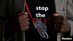 "FILE - A man's T-shirt reads ""Stop the Cut,"" referring to female genital mutilation, during a social event advocating against such practices at a school for girls in Imbirikani, Kenya, April 21, 2016."