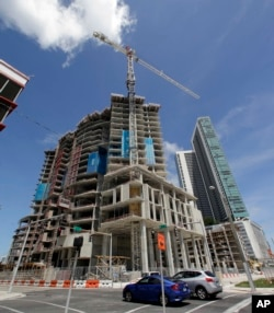 FILE - A high-rise building under construction is shown next to a high-rise condominium building, Sept. 7, 2017, in downtown Miami.