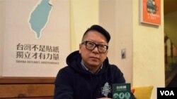 台灣社運人士、默契咖啡老闆陳致豪手持他設計的台灣國護照貼紙。(美國之音湯惠芸)