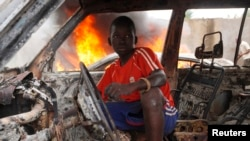 A Christian youth squats inside a burnt out car in Bangui December 10, 2013.