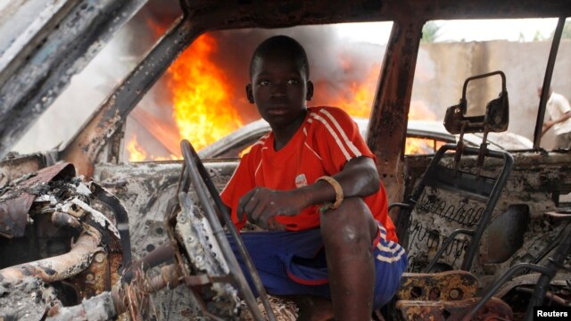 A Christian youth squats inside a burnt-out car in Bangui, Dec. 10, 2013.