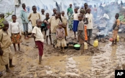 FILE - Refugee children stand in the mud near tents holding hundreds of other refugees who have fled from Burundi, at the Gashora refugee camp, in the Bugesera district of Rwanda, April 21, 2015.