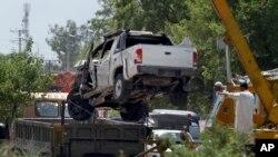 Sebuah mobil yang mengangkut perwira militer dipindahkan dari lokasi bom bunuh diri di Fateh Jang, sekitar 36 kilometer sebelah barat daya Islamabad, Pakistan, Rabu (4/6).