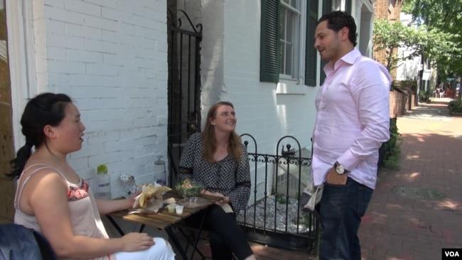 Falafel Inc. owner Ahmad Ashkar talks with customers outside the shop in Washington's Georgetown neighborhood. (J.Soh/VOA)