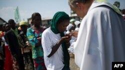 Un prêtre distribue l'eucharistie au cours d'une messe dans un camp des personnes déplacées à la périphérie de Goma, Nord-Kivu, 25 novembre 2012.