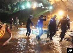 This undated from video released via the Thai NavySEAL Facebook Page, July 11, 2018, shows rescuers hold an evacuated boy inside the Tham Luang Nang Non cave in Mae Sai, Chiang Rai province, in northern Thailand.
