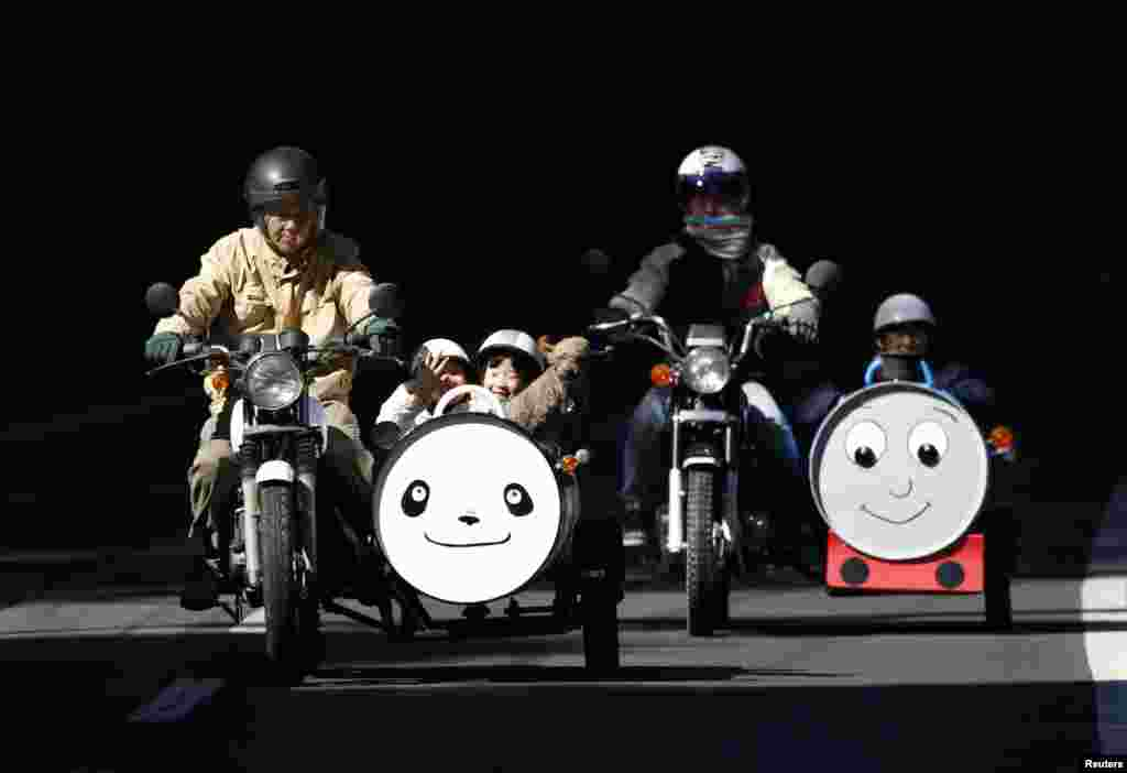 Sadao Kimbara (L) and his daughter-in-law Sayuri (2nd R) ride on Honda motorcycles with sidecars he made out of oil barrels, as his grandchildren Rio (2nd L), Ruka (C), pet dog Tida and Rui sit in the sidecars in Ome, pn the outskirts of Tokyo, Japan.