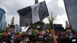 """Una persona sostiene una bandera negra de """"duelo"""" y flores durante una protesta por el asesinato del fotoperiodista Rubén Espinosa en el monumento Ángel de la Independencia de Ciudad de México, el 2 de agosto de 2015."""