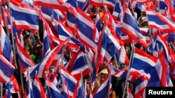 Anti-government protesters hold Thai national flags as they march towards the Department of Special Investigation (DSI) in Bangkok, Dec. 23, 2013.