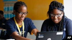 "Jahiem Johnson, 13, left, helps classmate Kamya Saunders, 13, as they work on an English passage during class at the Washington Leadership Academy in Washington, Aug. 23, 2017. The school utilizes ""personalized learning."""