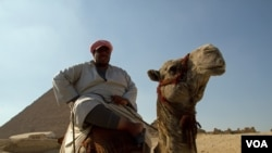 FILE - A man sits on his camel in front of the Pyramids at Giza, Egypt, July 13, 2013. (A. Arabasadi/VOA)