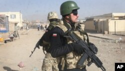 FILE - Polish NATO soldiers are seen patrolling in Ghazni, west of Kabul, Afghanistan, Dec. 21, 2011. Polish and Afghan special forces, backed by U.S. air power, freed 11 hostages held by the Taliban in Afghanistan's Helmand province, Poland's defense minister announced Tuesday.