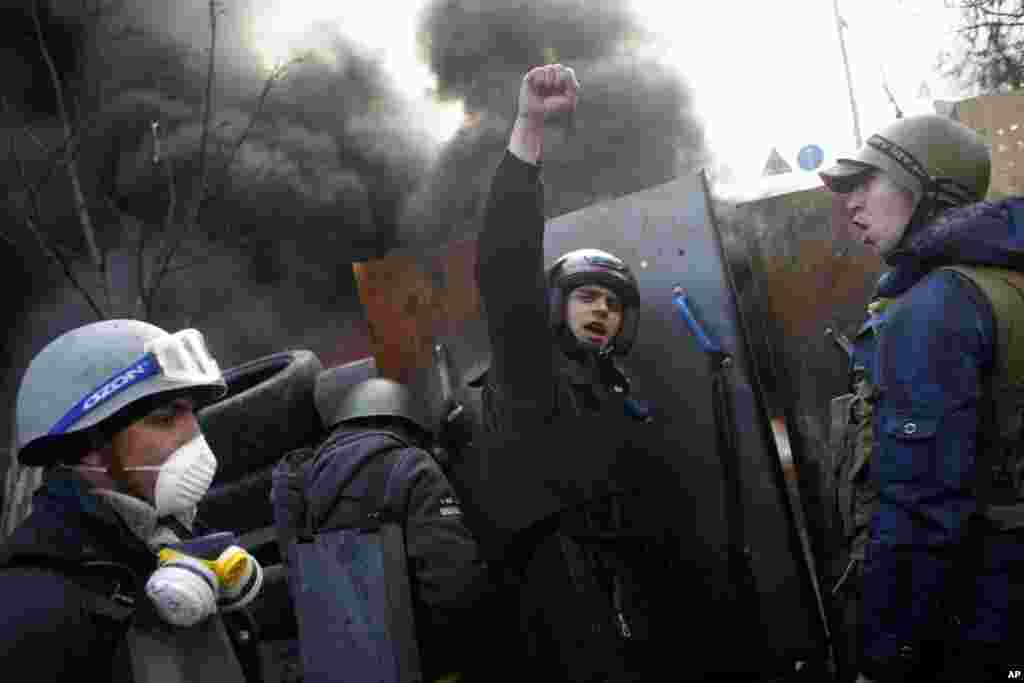 "Anti-government protesters shout ""Glory to the Ukraine"" as they man a barricade at Independence Square in Kyiv, Feb. 21, 2014."