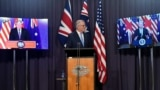 Australia's Prime Minister Scott Morrison, center, appears on stage with video links to Britain's Prime Minister Boris Johnson, left, and U.S. President Joe Biden at a joint press conference at Parliament House in Canberra, Thursday, Sept. 16, 2021.