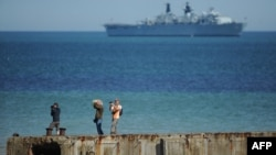 "FILE - People take pictures on a remain of the World War II ""Mulberry"" artificial harbour as a warship is anchored in the English Channel in Arromanches-les-Bains, Normandy."