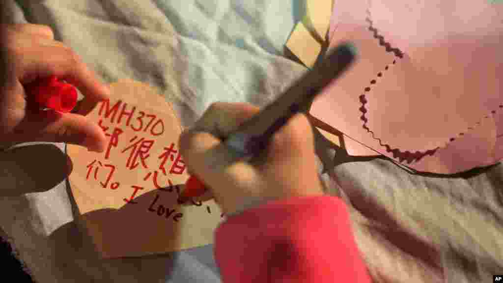 A girl writes a note which she will hang on a memorial for the people on Flight MH370 in Kuala Lumpur, March 30, 2014.
