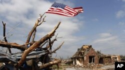 A United States flag tied to a tree branch waves in the wind over a business building destroyed by a tornado in Joplin, Missouri. Search teams accompanied by cadaver dogs on Tuesday picked their way through the rubble of thousands of homes and businesses