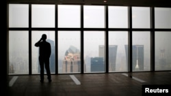 A man talks on a mobile phone as he looks at the view of the Shanghai skyline,