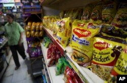 "Packaged food with ""Maggi"" sign on it are displayed at a grocery store in Bangalore, India."