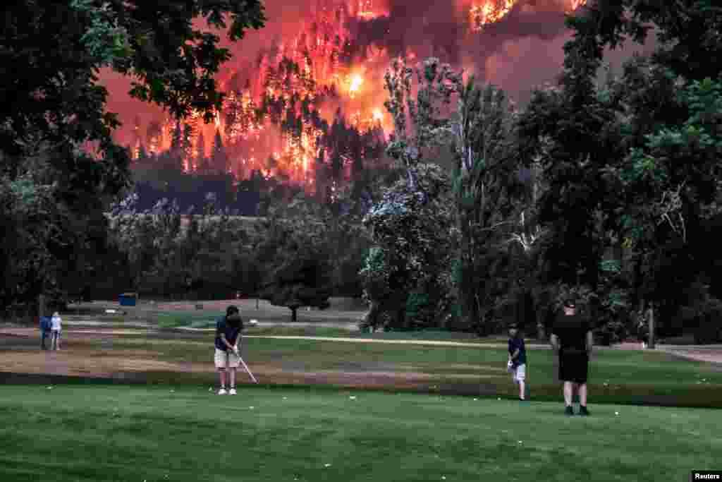 Incendio forestal de Eagle Creek mientras golfistas juegan en el campo de golf Beacon Rock en North Bonneville, Washington, EE.UU., 4 de septiembre de 2017.