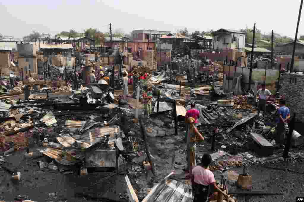Residents inspect burned ruins after an overnight fire that engulfed over 100 houses in Mandalay, Myanmar as the country continues to be in turmoil after the February military coup.