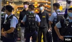 賢學思政召集人王逸戰(藍色口罩者)等4名成員以及3名市民共7人,被警察截查後被拘捕,12月1日凌晨全部獲准保釋。(美國之音特約記者湯惠芸攝)