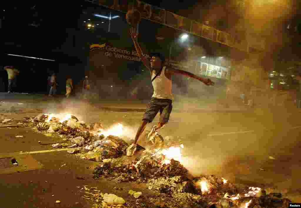 A man jumps over a barricade of burning garbage that supporters of opposition leader Henrique Capriles used to block a street, as they demonstrated for a recount of the votes in Sunday's election, in Caracas, April 15, 2013.