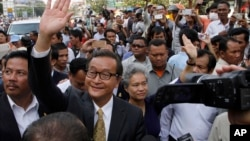 Sam Rainsy, front center, the head of the main opposition Cambodia National Rescue Party (CNRP) waves to the crowd before entering Phnom Penh Municipality Court in Phnom Penh, Cambodia, Tuesday, Jan. 14, 2014. Sam Rainsy and his party's Deputy President Kem Sokha appeared for questioning at the court about their possible involvement in inciting violence and social unrest, after four garment workers were brutality shot dead by government armed forces, on Jan. 3, according to a CNRP lawmaker. (AP Photo/Heng Sinith)