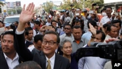 Sam Rainsy, front center, the head of the main opposition Cambodia National Rescue Party (CNRP) waves to the crowd before entering Phnom Penh Municipality Court in Phnom Penh, file photo.