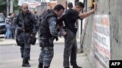 Cảnh sát lục soát một người đàn ông trong chiến dịch tiểu trừ các phần tử buôn ma túy trong khu ổ chuột Alemao ở Rio de Janeiro