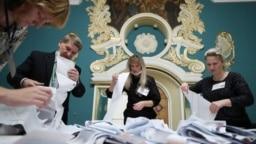 Para anggota KPU menghitung surat-surat suara di sebuah TPS dalam pemilu parlemen di Moskow, Rusia (19/9).