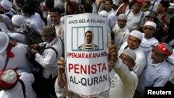 Seorang pengunjuk rasa mengacungkan poster dalam demonstrasi menuntut agar Gubernur Basuki Tjahaya Purnama atau Ahok ditangkap karena dinilai menista agama Islam, di Jakarta, 2 Desember 2016.