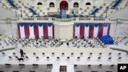 A law enforcement official sweeps a spectator seating area as preparations take place for President-elect Joe Biden's inauguration ceremony at the U.S. Capitol in Washington, Saturday, Jan. 16, 2021. (AP Photo/Patrick Semansky)