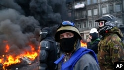 Người biểu tình đứng sau rào chắn trước cảnh sát ở trung tâm Kyiv, ngày 25 tháng 1, 2014.