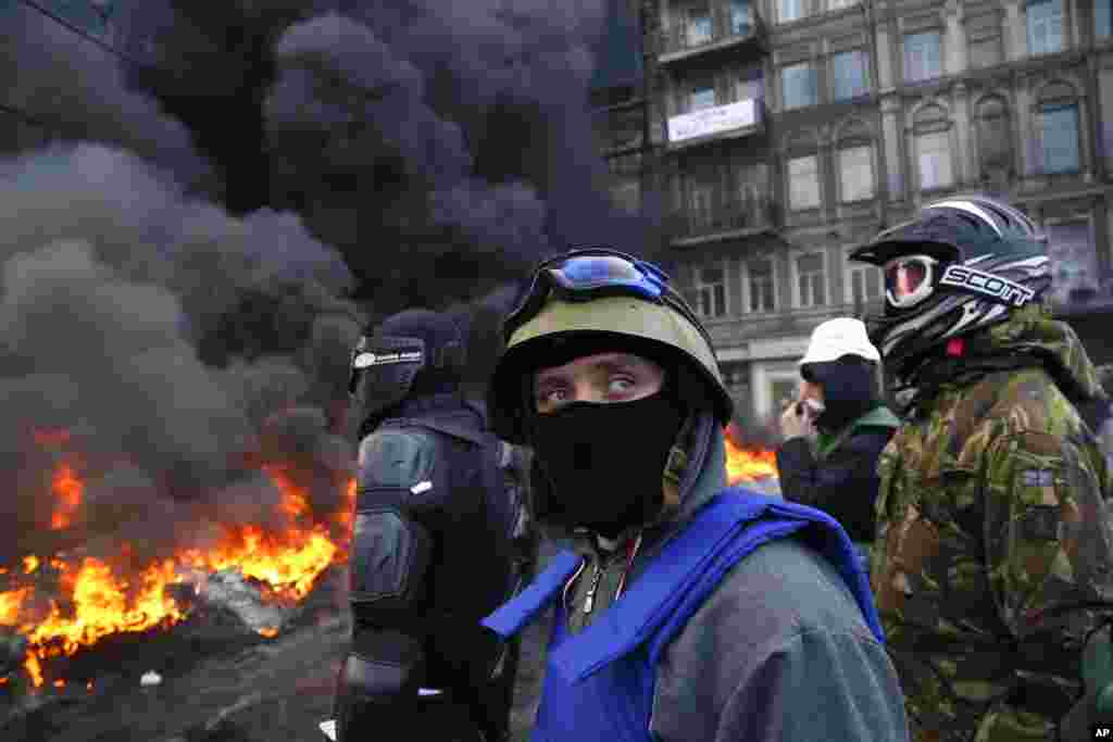 Protesters stand behind the barricade in front of riot police in central Kiev, Ukraine.