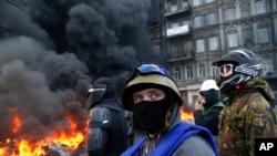 Demonstran berdiri di belakang barikade polisi anti huru-hara di Kiev, Ukraina, 25 Januari 2014.