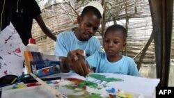 Un homme aide un enfant autiste à peindre lors de la Journée mondiale de l'autisme, à Abidjan le 2 avril 2017 (Photo d'illustration)