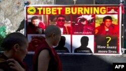 """Hai nhà sư đi ngang qua một biểu ngữ """"Tây Tạng đang bốc cháy"""" với hình ảnh các tăng sĩ đã tự thiêu. Kể từ tháng Ba năm 2011, đã có 20 người tự thiêu để phản đối việc Trung Quốc đàn áp văn hóa và tôn giáo của người Tây Tạng"""