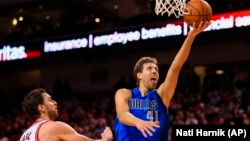 Dallas Mavericks' Dirk Nowitzki (41) goes for a layup against the Chicago Bulls' Pau Gasol (16) during the second half of an NBA preseason basketball game in Lincoln, Neb., Friday, Oct. 23, 2015.