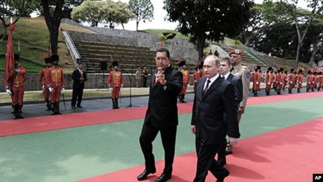 Venezuelan President Hugo Chavez (L) and Russian Prime Minister Vladimir Putin receive military honors at the Presidential palace Miraflores in Caracas, 02 Apr 2010
