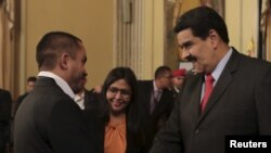President Nicolas Maduro (R) and Venezuela's new Minister for Economy and Productivity, Luis Salas, shake hands Jan. 6, 2016, at a meeting at Miraflores Palace in Caracas.