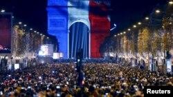 Warga Paris menghadiri perayaan tahun baru di Arc de Triomphe, yang diterangi cahaya lampu berwarna bendera Perancis Kamis malam (31/12).