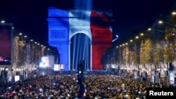 Revelers gather near the Arc de Triomphe, lit in the colors of the French flag, on the Champs Elysees in Paris during New Year's celebrations, Dec. 31, 2015.